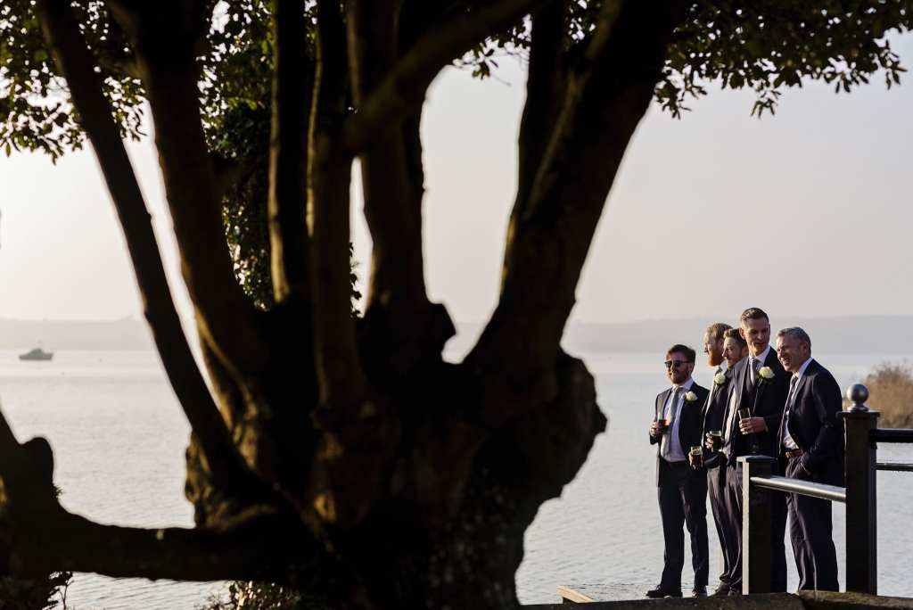 groom stands with ushers and father on dock during groom prep at Christchurch Habour Hotel & Spa