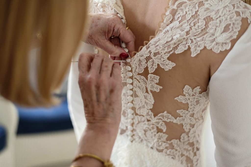 mother of the bride uses crochet hook to fasten buttons on chic New Forest wedding gown during bridal prep at Christchurch Habour Hotel & Spa