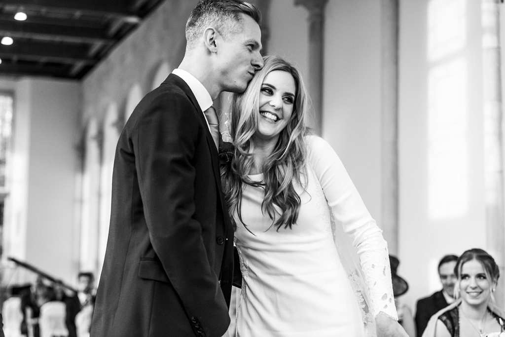 groom kisses bride on head after first kiss during chic New Forest wedding at Highcliffe Castle