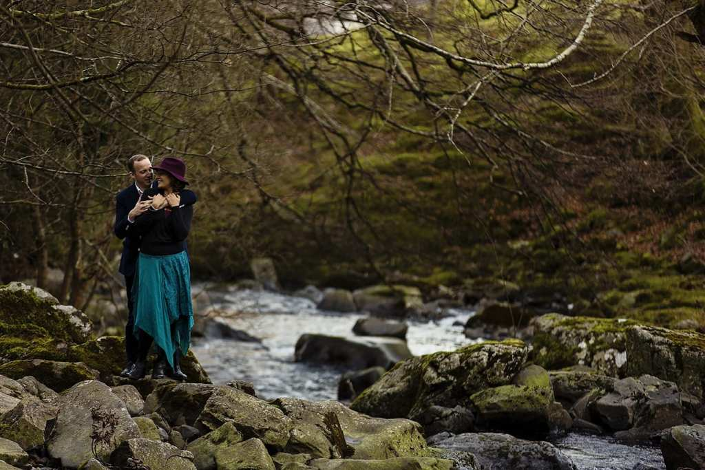 couple cuddle next to Llanberis river during Snowdonia portrait session