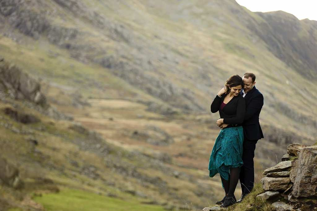 woman holds hair out of face while husband holds her during Snowdonia portrait session