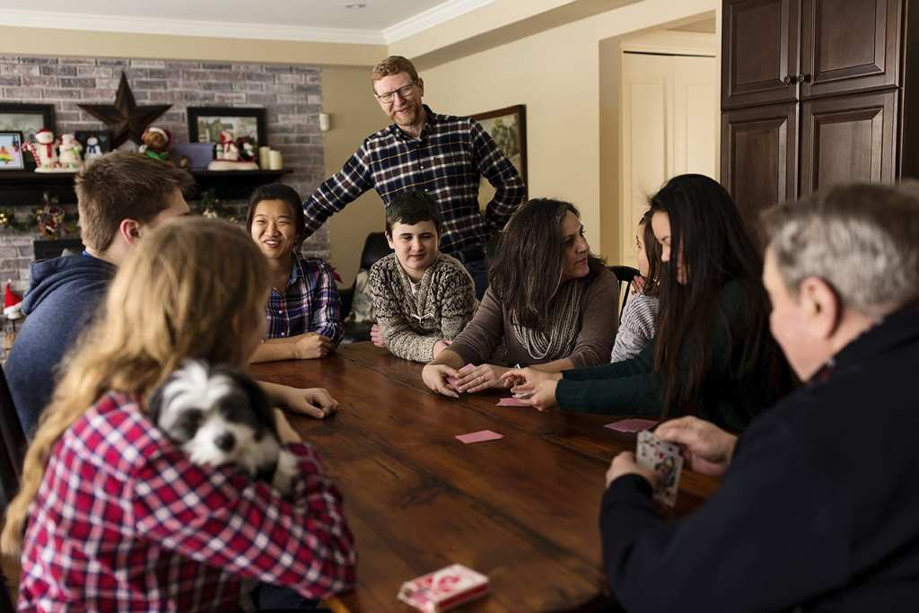 large family gathers around kitchen table to play cards