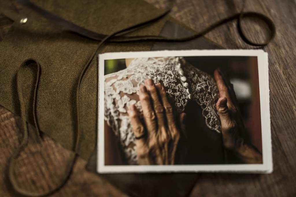 Modern Ontario wedding photos printed on fine art matte paper resting on top of dark leather satchel