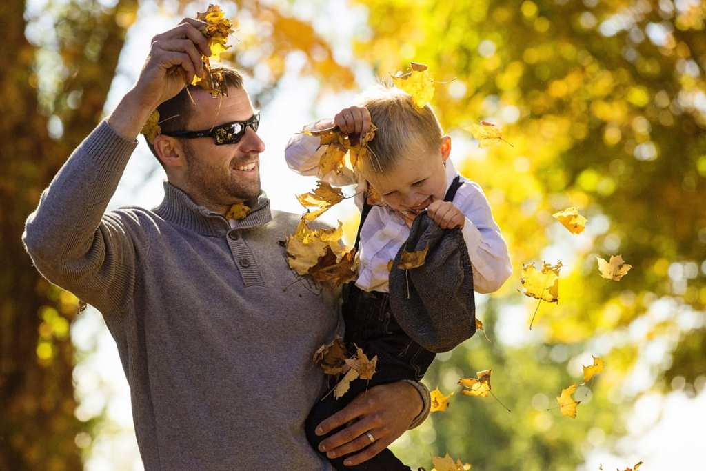 dad throws leaves on son's head while holding him during session with ontario family phtographer