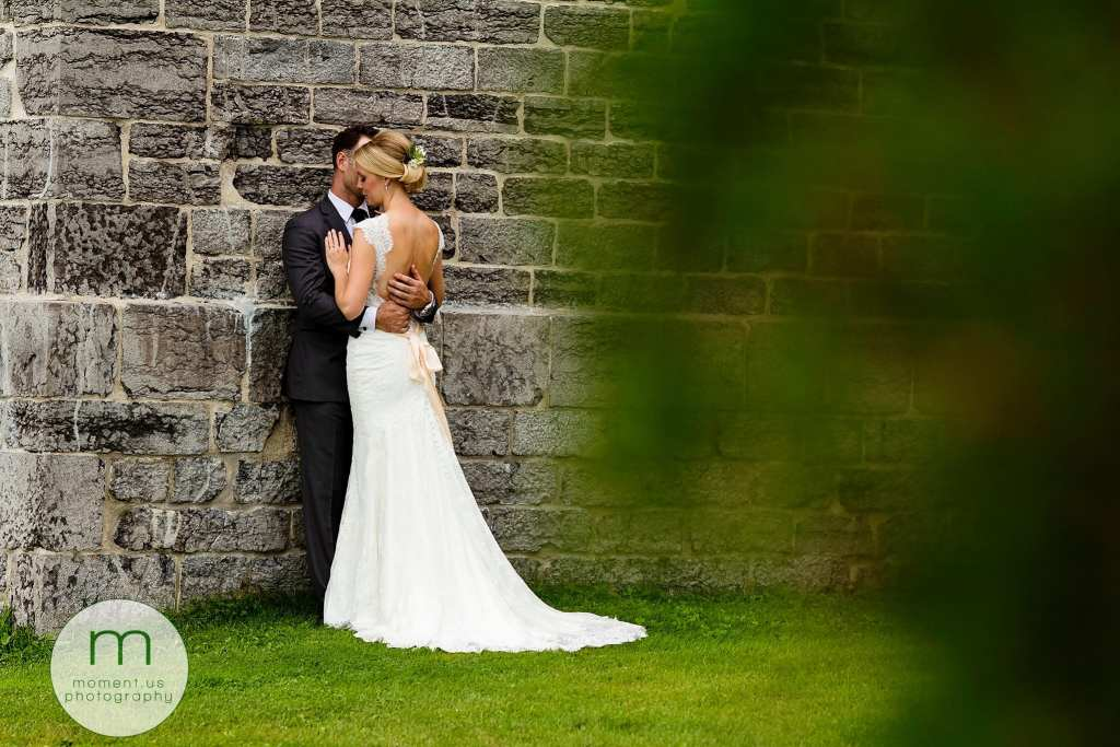 groom leans against stone wall and holds bride close during Ontario & Quebec Wedding Photography portraits