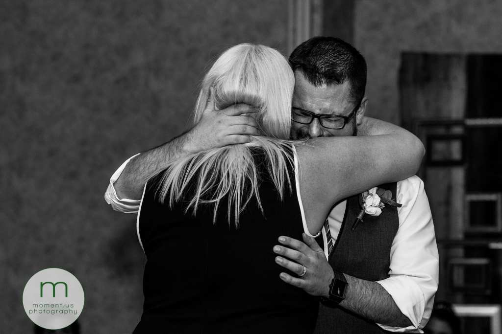 crying groom hugs sister during first dance