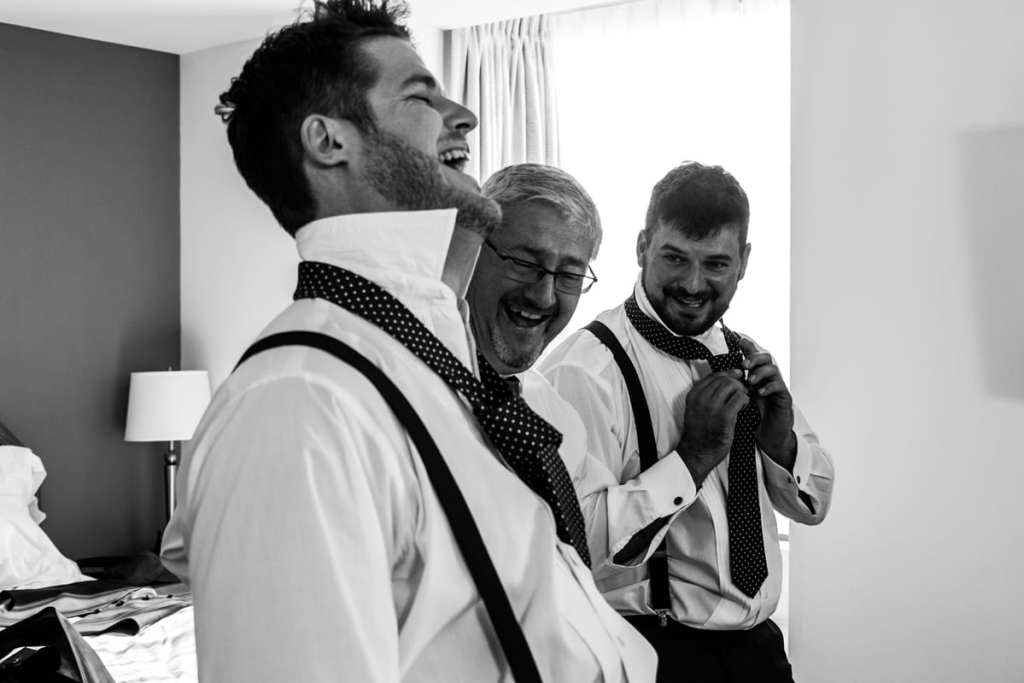 groomsman and father laugh at groomsman who can't tie his tie