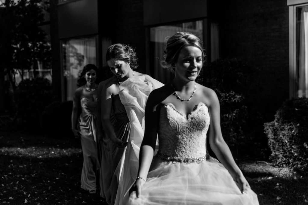 bridesmaids help bride carry dress in dramatic sunlight for Autumnal NAV Centre Cornwall Wedding
