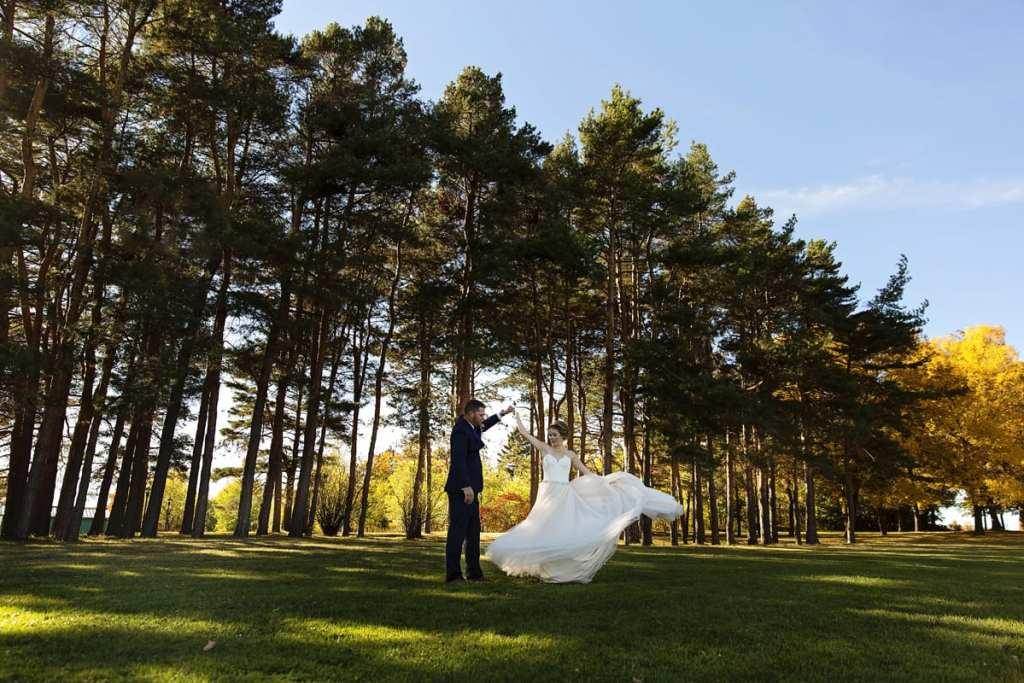 groom twirls bride in blush wedding dress in front of pines