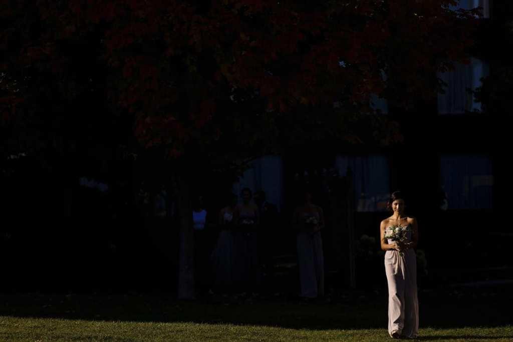 bridesmaid walks down aisle in dramatic sunlight for Autumnal NAV Centre Cornwall Wedding