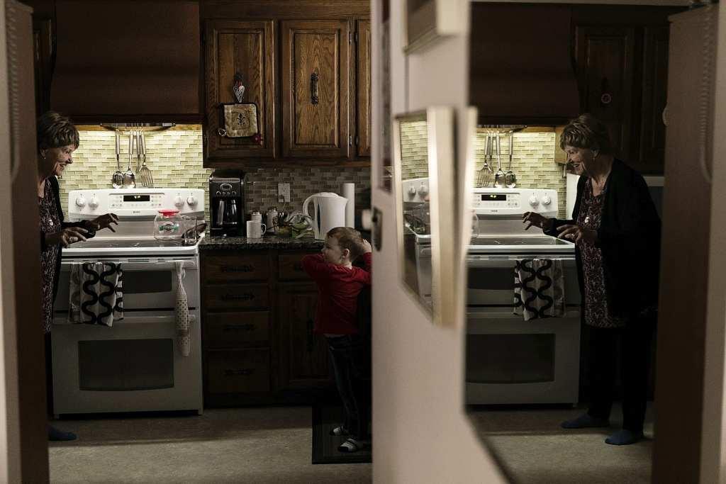 Grandma facing little boy in kitchen making monster hands