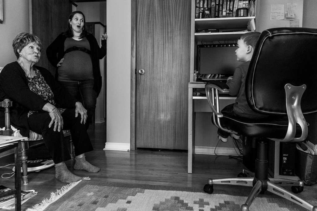 mother and grandma look surprised while talking to boy in office chair during Ontario Family Photojournalism session