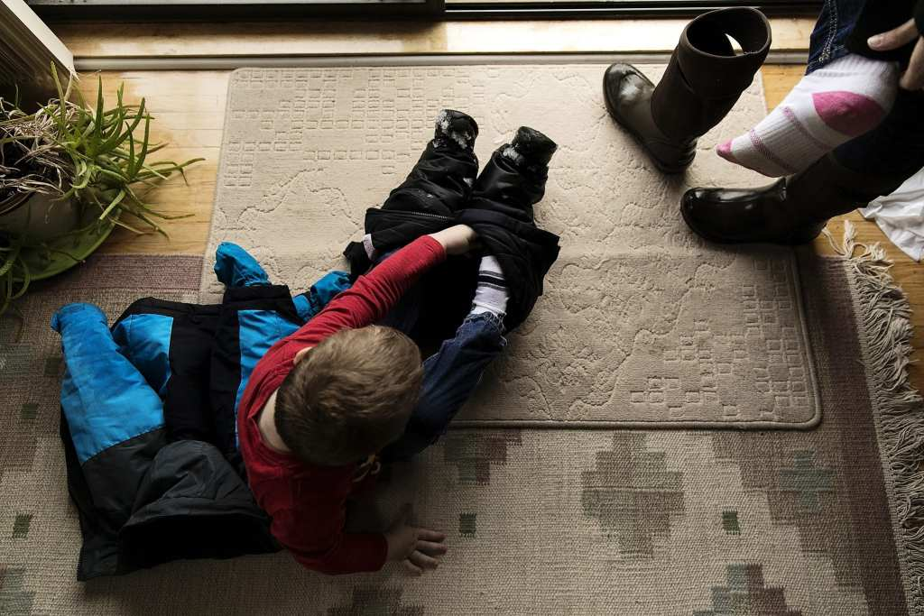 boy puts on snow boots while mother does the same beside him