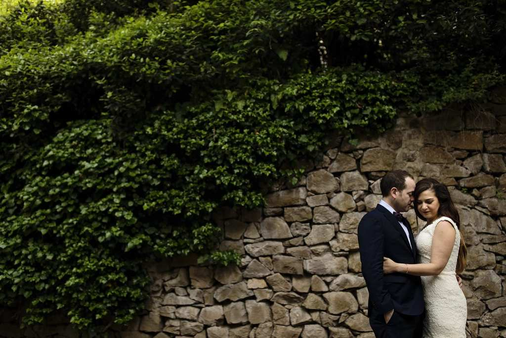 bride and groom snuggle in front of stone wall covered with ivy during session with Ontario & Destination Wedding Photographer