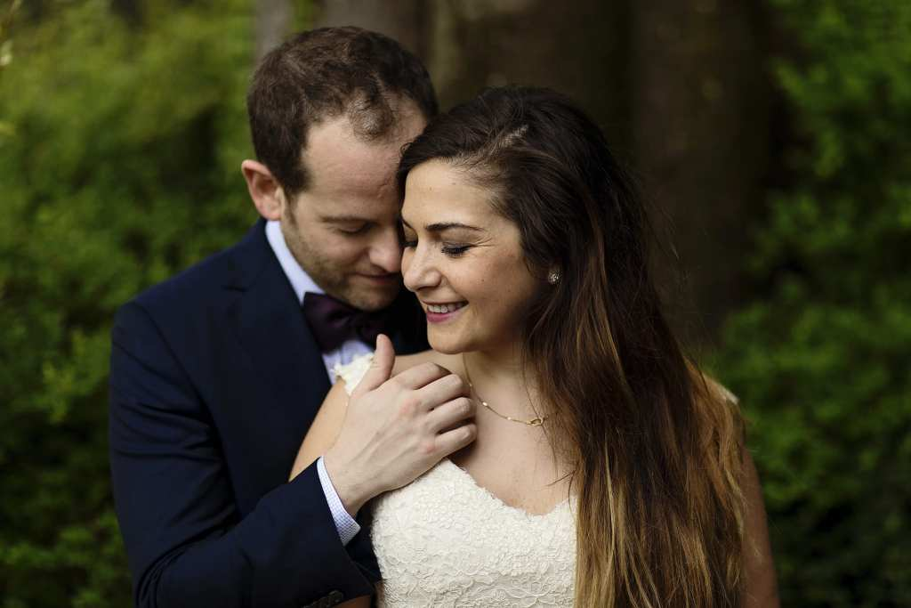 groom strokes bride's collarbone while standing behind her during session with Ontario & Destination Wedding Photographer