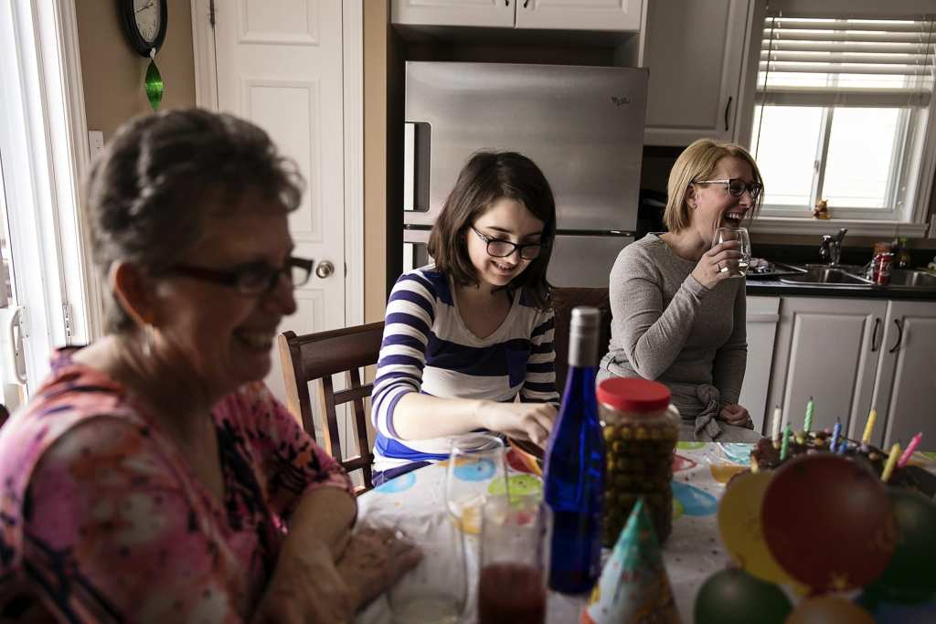 women laughing together around kitchen table during Eastern Ontario family photojournalism session