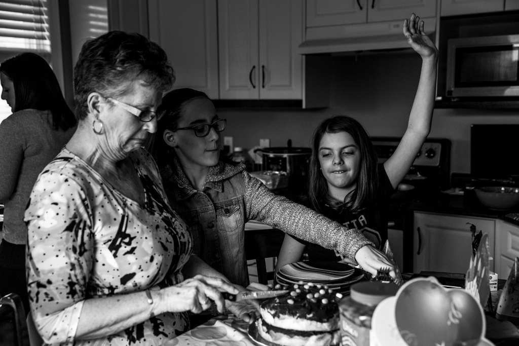 grandma slices cake while granddaughter raises hand to show she wants some
