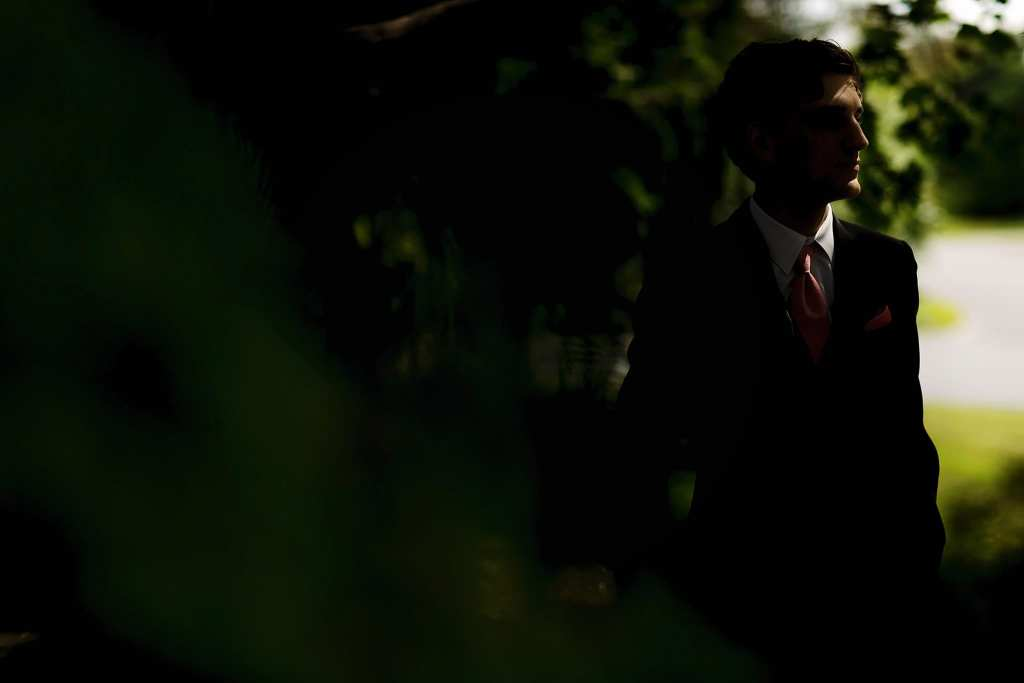 groom stands in deep shadow on day of Strathmere wedding