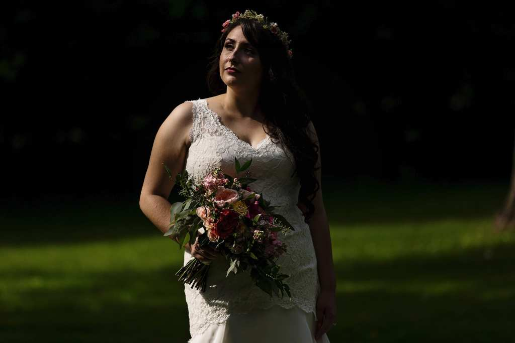 bride stands in sunshine holding bouquet