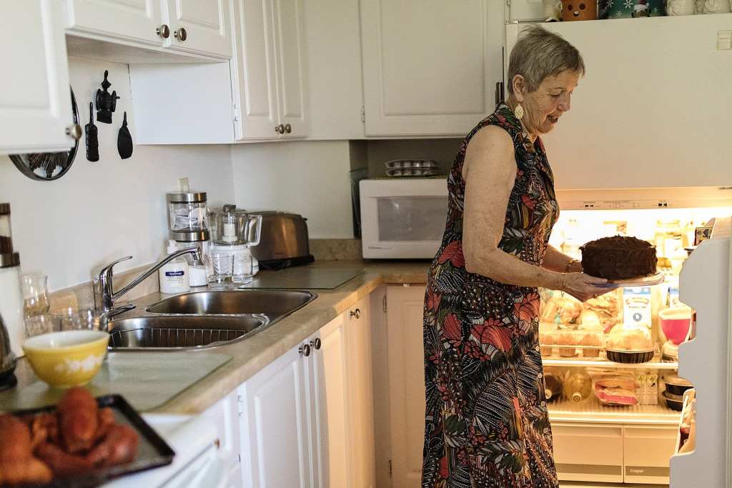 grandmother takes cake out of fridge