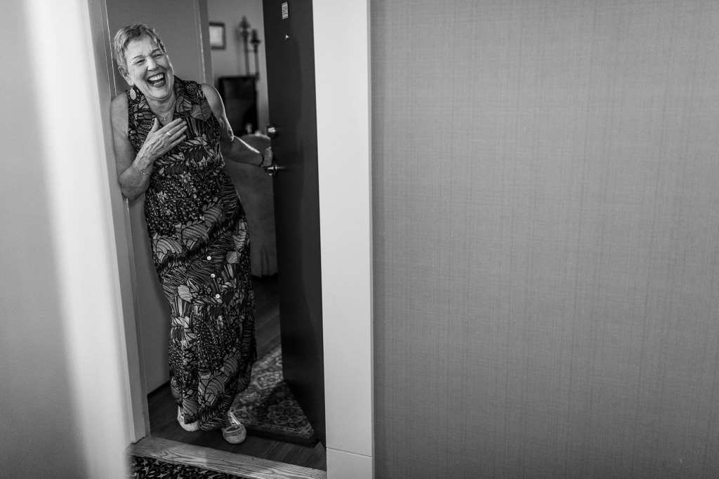 grandmother laughs in doorway with hand to chest
