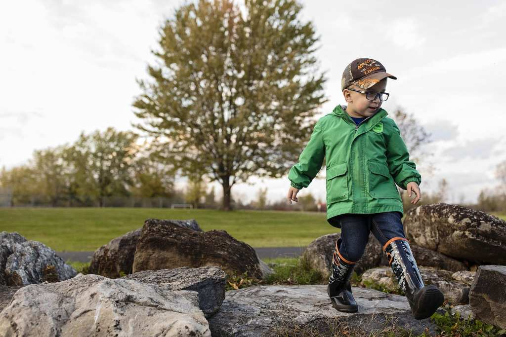 boy in rubber boots walkes over rocks with fall colours in tree behind him