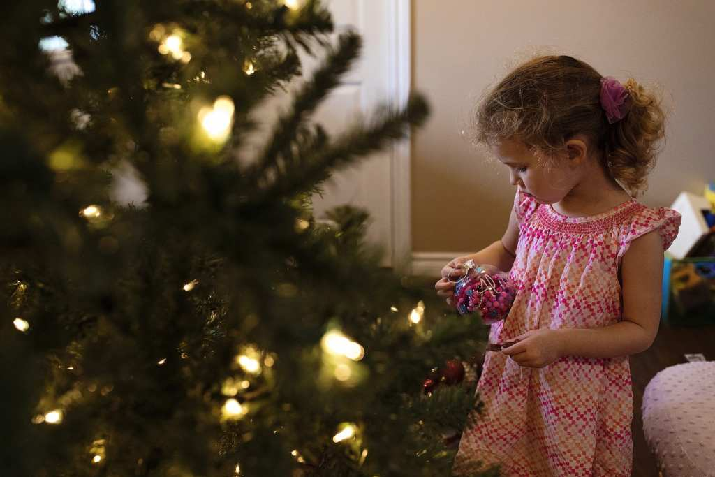 Girls stands in front of tree holding ornament as part of Cornwall family Christmas preparations