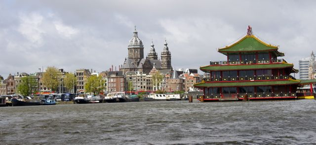 Town hall and Chinese center seen from a canal in Amsterdam.
