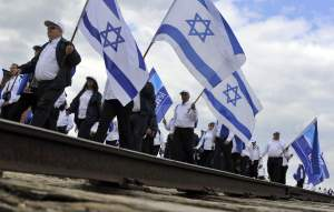 Participants of the traditional 'March of the Living' walk behind a railway track inside the former Auschwitz-Birkenau Nazi Death Camp near Oswiecim, southern Poland, Monday, May 2, 2011. Thousands of people from around the world take part in the annual March of the Living paying tribute to the victims of the Holocaust at the former Nazi Death Camp Auschwitz-Birkenau.  (AP Photo/Bela Szandelszky)