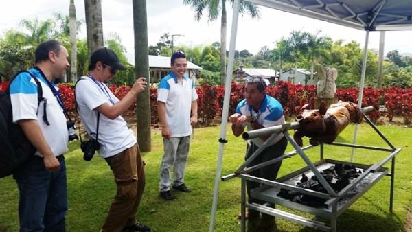Periodistas colombianos y un funcionario de Hyundai bromean durante su primer encuentro con un lechón asa'o boricua.
