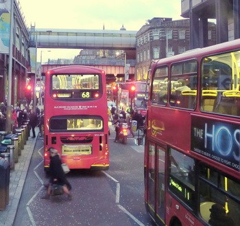 red double-decker London buses line a busy street