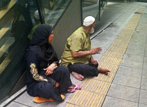 This couple does not appear to be hungry or homeless, but they were begging near KL Sentral.