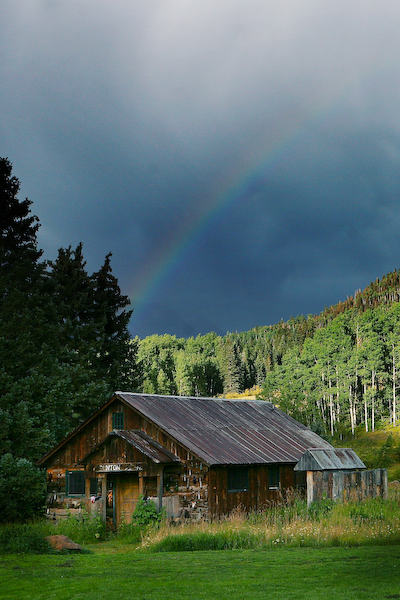 rainbow over a rustic cabin