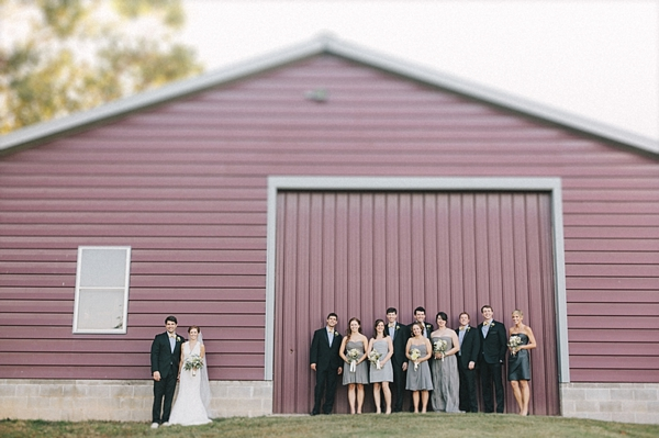 bridal party in front of barn