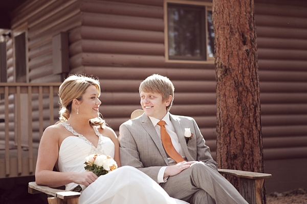 estes park bride and groom share a moment on a wooden bench