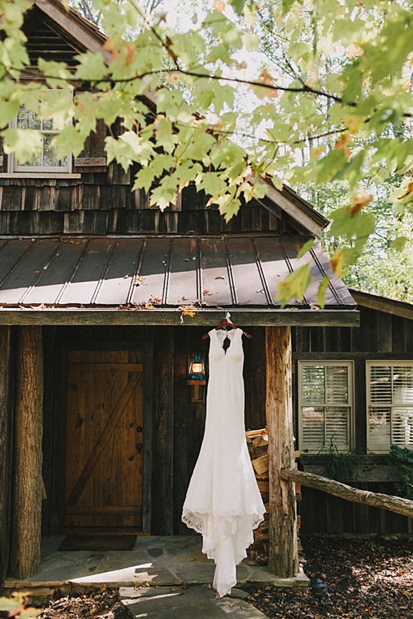 lace wedding gown hanging from a rustic cabin