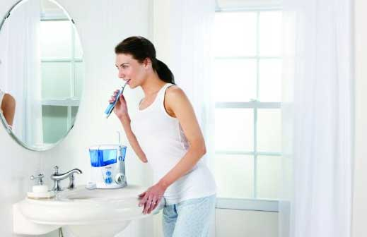 Woman using a Waterpik WP-900 in bathroom.