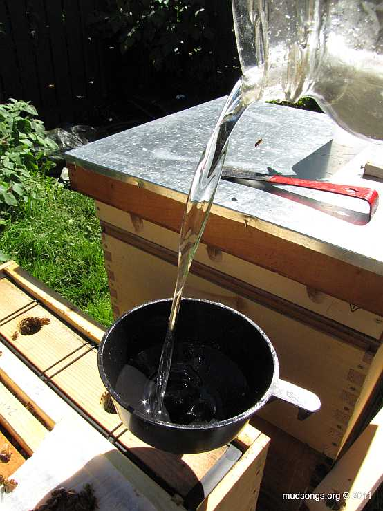 Filling a frame feeder with sugar syrup. (August 27, 2011.)