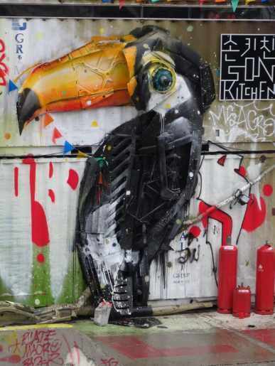 """Werk aus der Serie """"Trash Animals"""" von Bordalo II – Die Werke bestehen zum Großteil aus Schrott und schwer-recycelbaren Materialien. Der Künstler will hiermit auf die Verschmutzung der Umwelt durch die Verschwendung von Materialien aufmerksam machen. Der Tukan befindet sich in Berlin."""