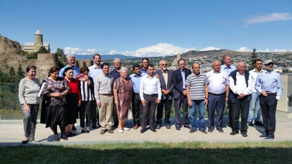 The Caucasus Regional Meeting Participants pose on balcony at the of Institute of Botany. The ancient Narikala Fortress of Tbilisi is in the background.