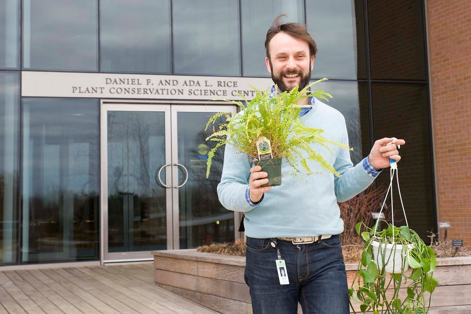 PHOTO: Dr. Fant carries a fern and a pothos plants out of the Plant Conservation Science Center.