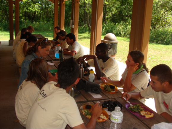 PHOTO: Staff and crew feast at picnic tables in the shade on a sunny day.