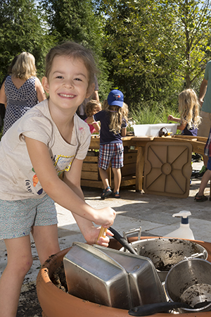 PHOTO: Gemma plays in the outdoor mud kitchen.