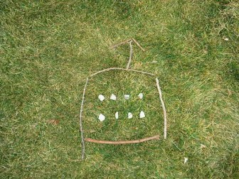 PHOTO: four sticks are arranged to form a square with eight stones inside the square; three sticks form an arrow over the square to tell what direction the hiker should take.
