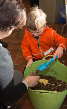 PHOTO: A low, wide trug full of soil makes filling pots easy for younger gardeners.