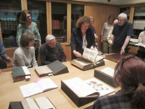 PHOTO: A meeting with a dozen people gatherered around rare books.