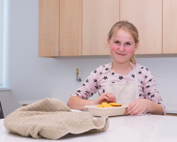 a girls is smiling as she holds the plate of muffins she made, and is going to taste.
