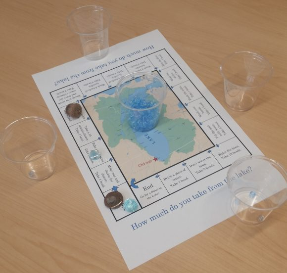 Board, cups, beads, and game tokens are arranged for the water conservation game.