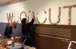 "It took 1,022 wood ""cookies,"" 3 people, and 3 blisters to install the exhibition's title."