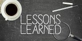 43973035 - lessons learned concept on black blackboard with coffee cupt and paper plane